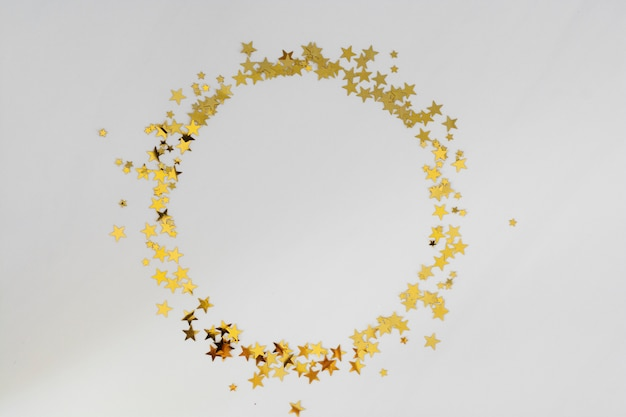 Golden glitter frame circle, confetti stars isolated on white background. christmas, party or birthday background.