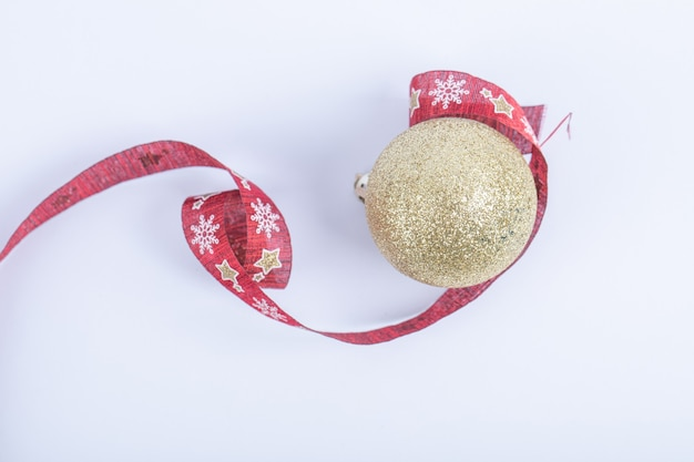 A golden glittering ball with red christmas ribbon on the white