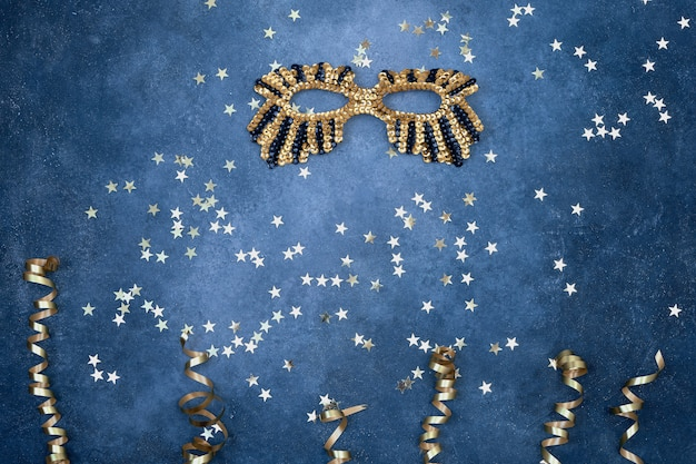 Golden glittering mask and serpentine with golden stars on blue.