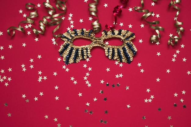 Golden glittering mask and serpentine with golden stars on red.