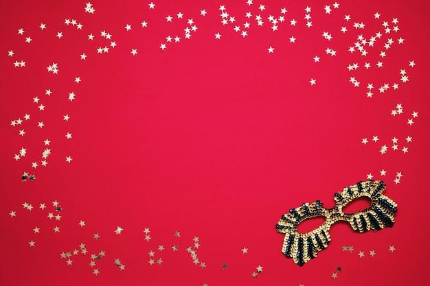 붉은 벽에 황금 별을 가진 황금 빛나는 마스크. 상위 뷰, 복사 공간.