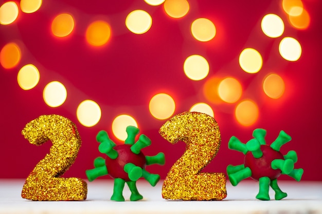 Golden glittering numbers 2020 with covid-19 virus with bokeh on red background. copy space.