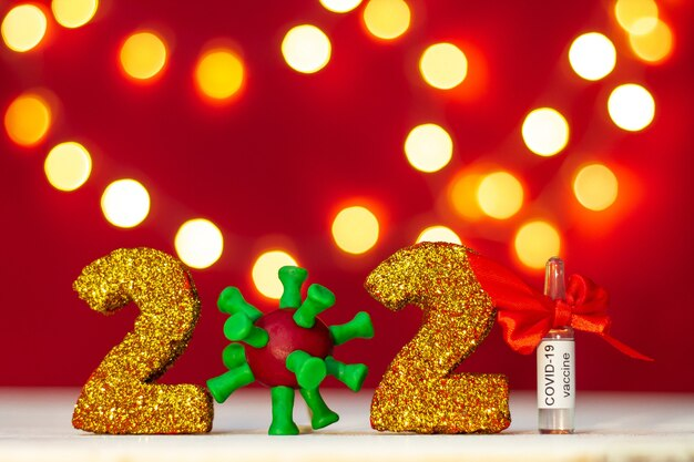 Golden glittering numbers 2021 with covid-19 virus and vaccine ampoule with bokeh on red background. copy space.