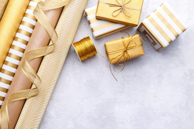 Golden glossy wrapping paper rolls and gift boxes