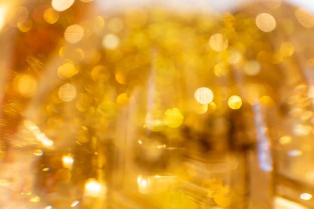 金色に輝くボケ味の背景。抽象的な明るくきらびやかな背景。焦点がぼけた画像。