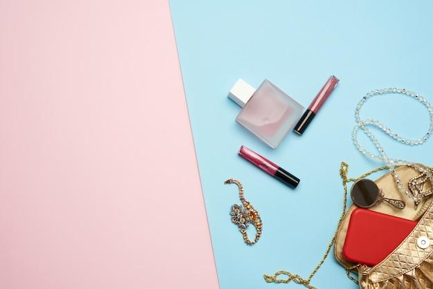 Golden handbag, lip gloss and beads on a blue background