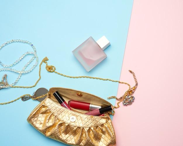 Golden handbag, lip gloss and beads, top view