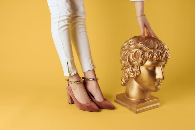 黄金の頭の彫刻の女性の足は黄色の壁をファッションします。