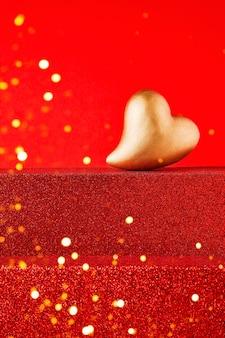 Золотое сердце на ярко-красном подиуме с копией пространства. концепция празднования дня святого валентина