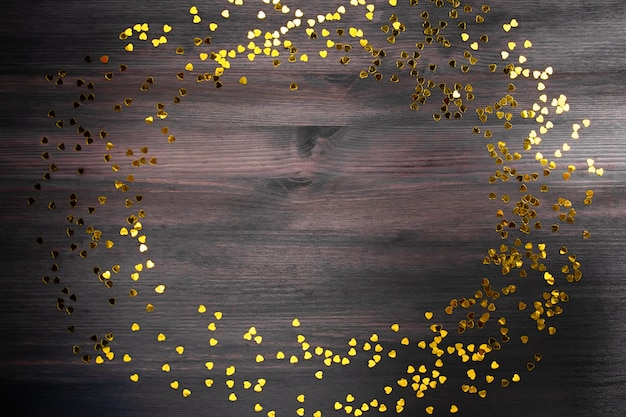 Golden heart shaped confetti frame on dark wooden background, copy space
