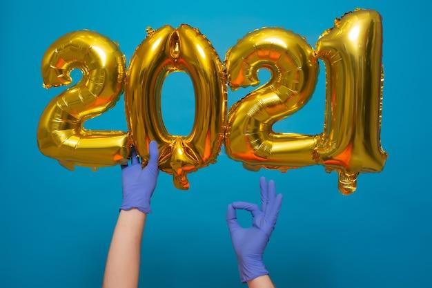 Golden helium balloons with numbers 2021 near christmas tree isolated on blue background. coronavirus.