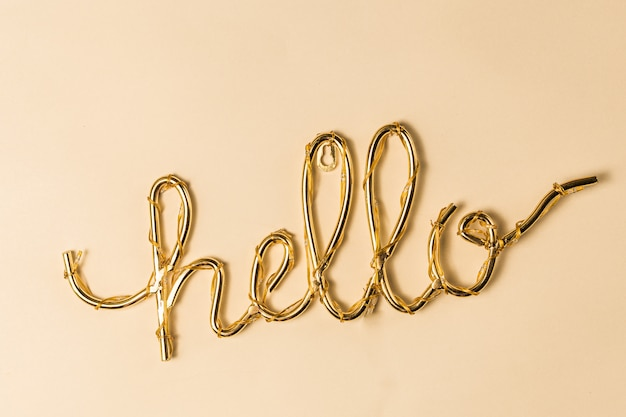 Golden hello sign on a bright surface