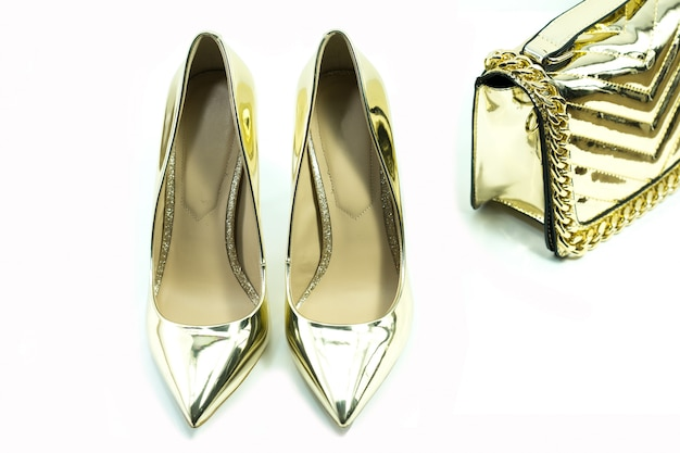 Golden high heel shoes and bag for lady isolated