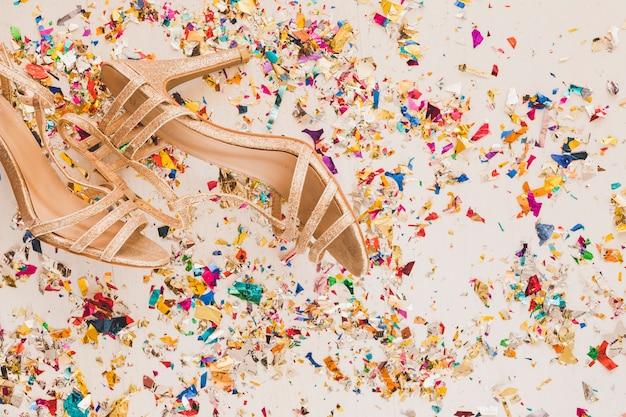 Golden high heels on pile of glitter