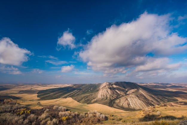 Золотые холмы, маленькие горы на фоне голубого неба с облаками