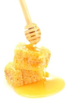 Золотые соты и деревянные моросилки с медом на белом