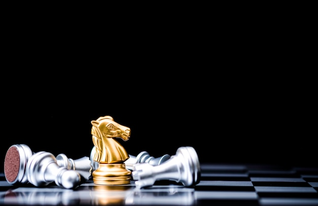 黄金の馬のチェスは、倒れた銀のチェスの駒で一人で立っています。ビジネス競争とマーケティング戦略計画コンセプトの勝者。