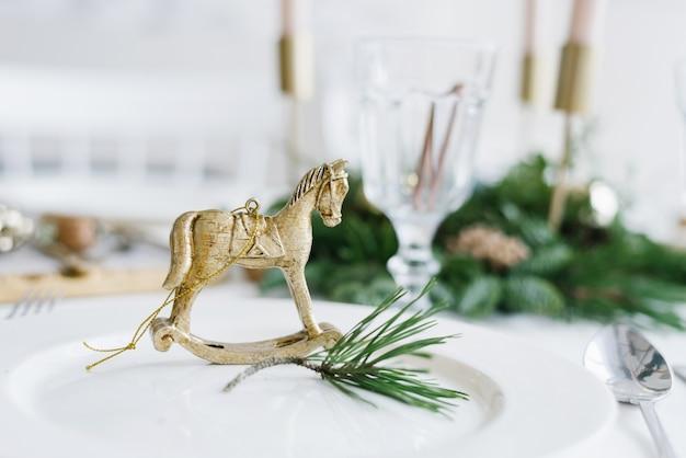 Золотой конь на белой тарелке с веточкой сосны
