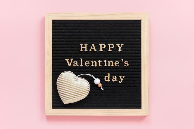 Золотая надпись с днем святого валентина и украшения текстильного сердца на доске черного письма, центральная композиция на розовом фоне.