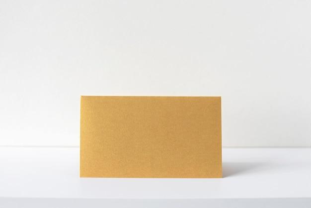 흰색 책상, 베이지색 인테리어에 황금 초대 또는 인사말 카드. 빈 테이블에 빈 정사각형 종이 시트. 모형, 텍스트를 위한 공간입니다.