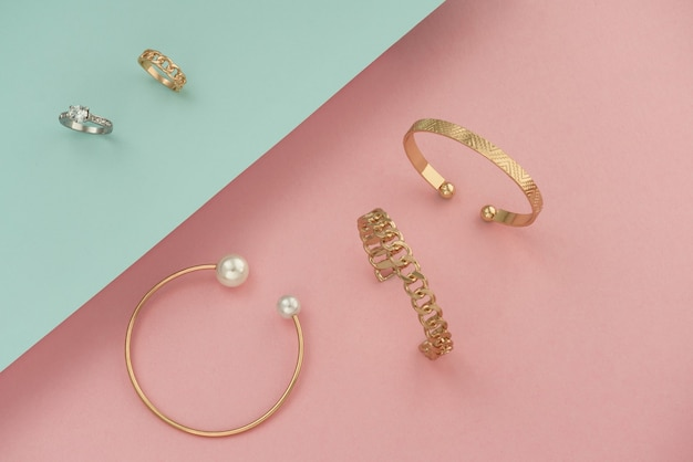 Golden jewelries bracelets and rings on pink and blue background