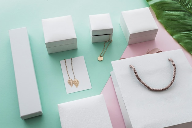 Golden jewelry boxes with shopping bag on pastel background