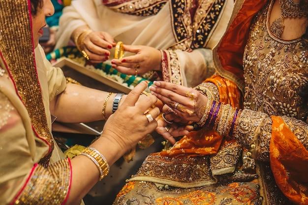 ヘナと女性の手に金色の宝石のブレスレットとリング