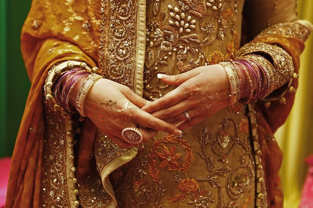 Golden jewelry bracelets and rings in woman's hands with henna