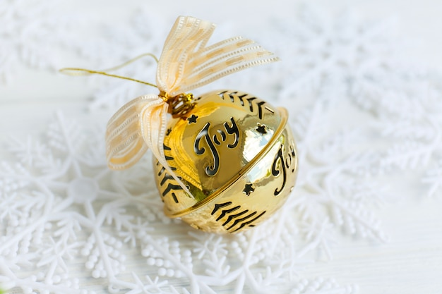 Golden jingle bell christmas bauble with text joy gold ribbon snowy abstract background and snowflakes.