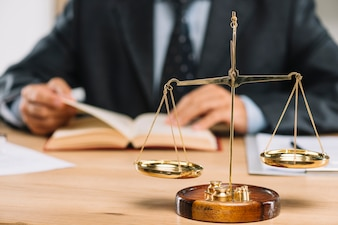 Golden justice scale in front of lawyer reading book on table