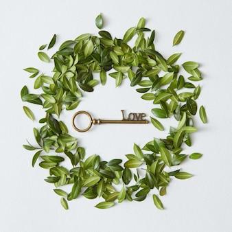 흰색 배경 위에 녹색 잎으로 만든 중간 또는 원으로 표시되는 황금 열쇠. 녹색 잎 개념입니다.