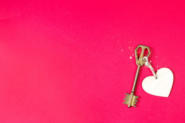 Golden key with wooden tag in the shape of a heart on a red background