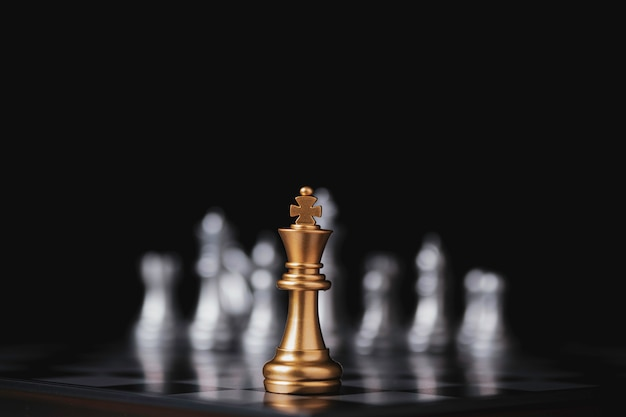 Golden king chess in front of silver pawn chess on chess board and black background.