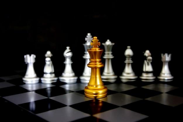 Шахматы золотой король перед шахматными фигурами на шахматной игровой доске