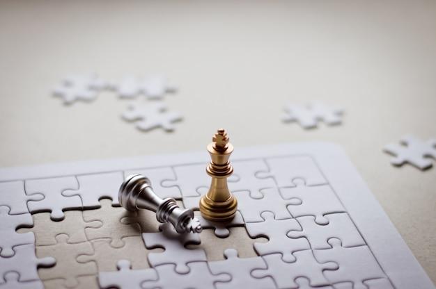ゴールデンキングチェスピースはビジネスと金融のためのジグソーパズルでシルバーキングチェスを獲得する。