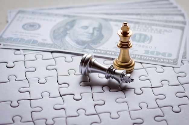 Golden king chess piece win with puzzle, banknotes background for business and financial.