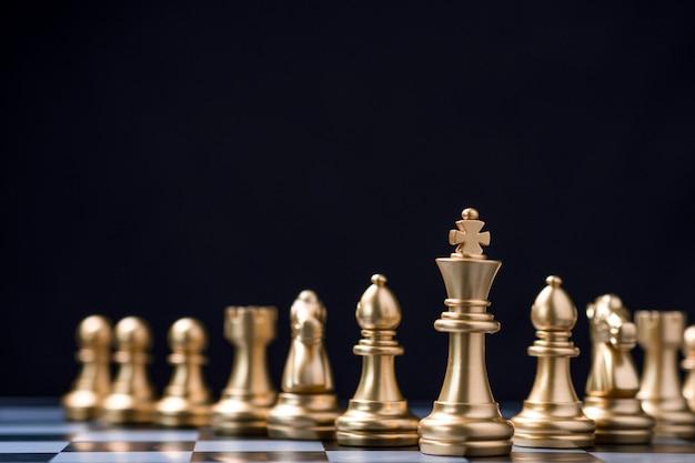 ゴールデンキングチェスは他のチェスの駒の前に立っています。リーダーシップビジネスチームワークとマーケティング戦略計画コンセプト。