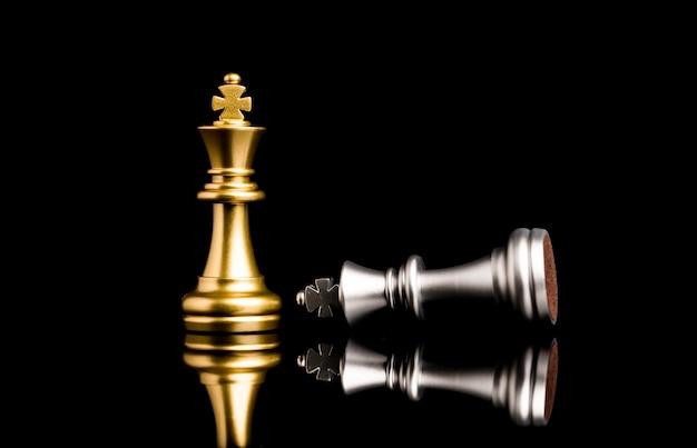 Золотой король шахмат стоя и серебряный король шахматы падают на победителя, бизнес-конкурента и концепции стратегии.