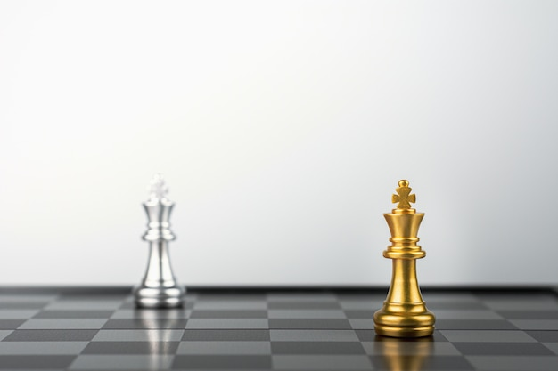 Golden king chess standing encounter silver king enemies.