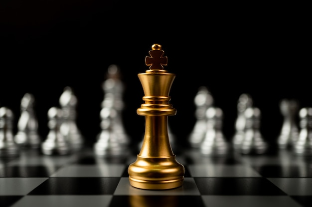 Golden king chess standing in front of other chess