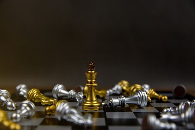 The golden king chess standing in the middle of other chess is falling.