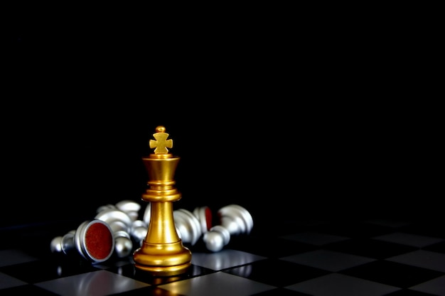 Золотой король шахмат, стоя с шахматными фигурами, лежа на доске, изолировать на черном фоне