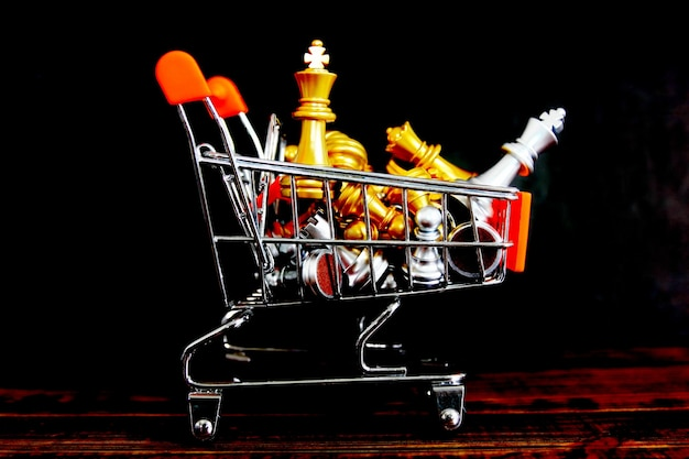 Golden king chess with chess pieces in small shopping cart om retro wood floor isolate on black