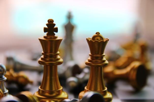 Golden king and queen chess standing among falling chess on chess board