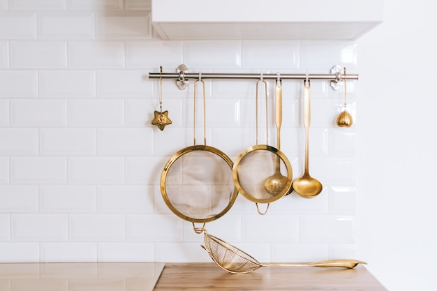 Golden kitchen utensils for cooking on a white wall with copy space.