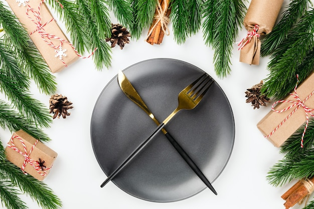 Golden knife and fork crossed on black plate on christmas dinner table with frame of fir branches wi...