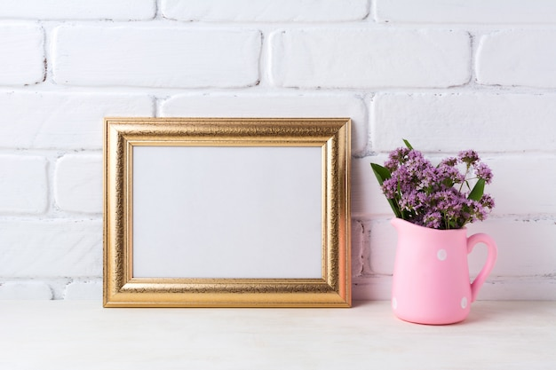 Golden  landscape frame  with purple flowers in pink rustic pitcher