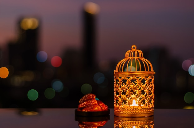 Golden lantern and dates fruit with dusk sky for ramadan kareem.