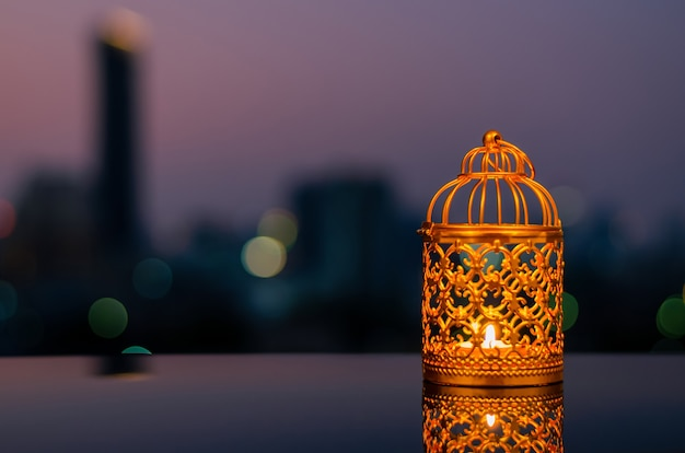 Golden lanterns with dusk sky and city bokeh light for ramadan kareem.
