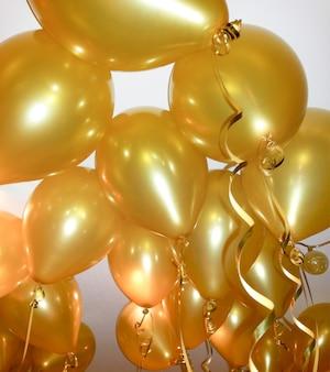 金のリボンのクローズアップと金色の大きな風船。スペースをコピーします。